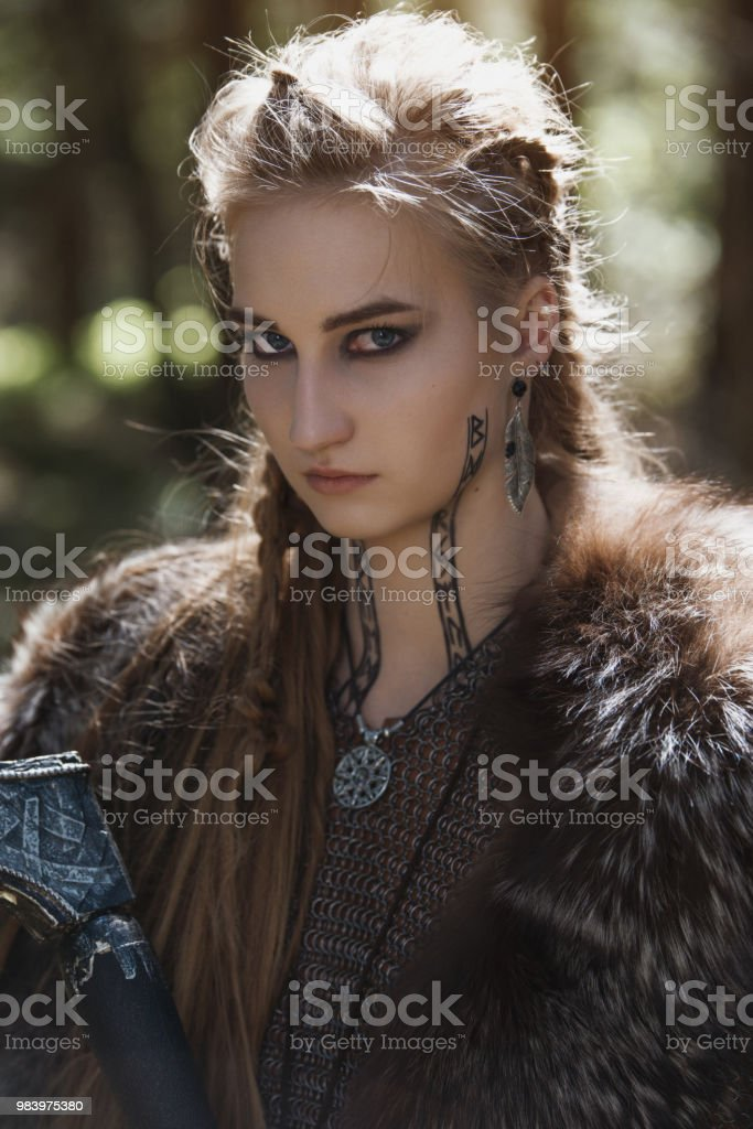 Viking woman with hammer wearing traditional warrior clothes in a deep mysterious forest. stock photo