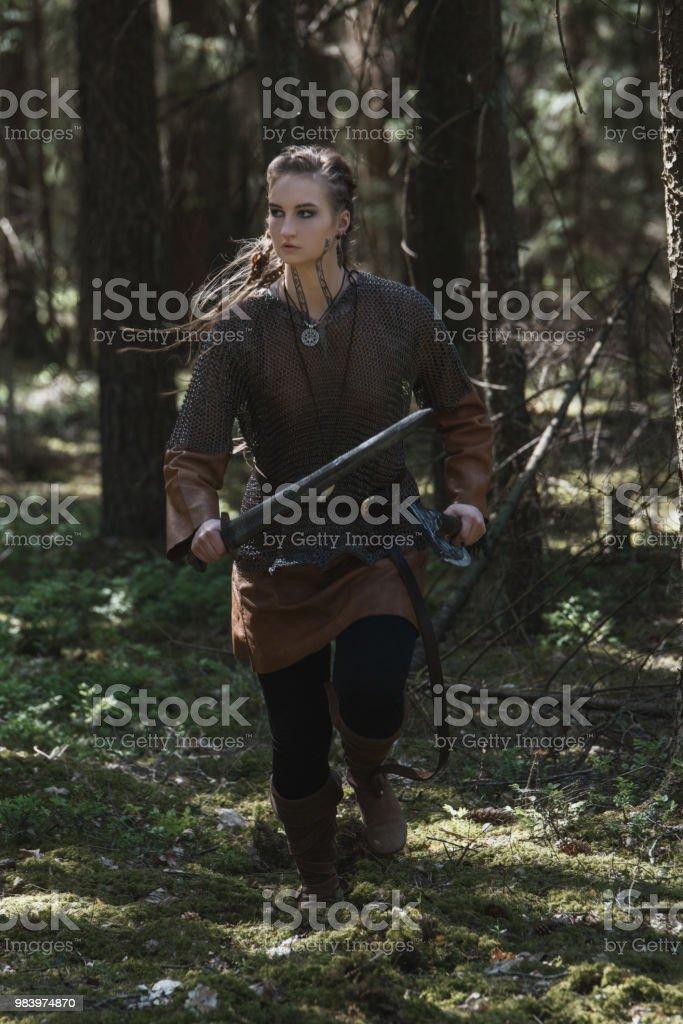 Mulher de Viking com espada e martelo, vestindo roupas de guerreiro tradicional em uma floresta profunda, misteriosa. - foto de acervo