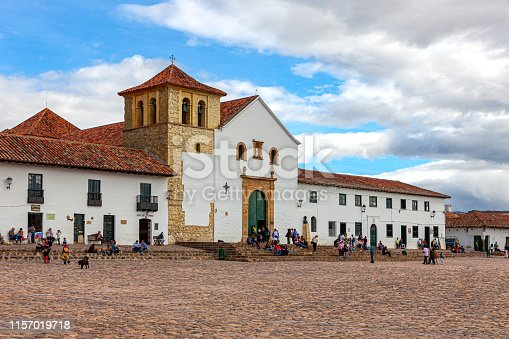 Villa de Leyva, Colombia - The church on the Plaza Mayor of the historic 16th Century town of Villa de Leyva. Founded in 1572 and located at an altitude of just over 7000 feet above mean sea level on the Andes Mountains, Villa de Leyva was declared a National Monument by the Colombian Government in 1954 to protect its colonial architecture and heritage. It is located in the Department of Boyacá. The square is the largest town square in Colombia. Colombians visiting the town and local residents are seen on the square just sitting and relaxing, chatting with friends or going about their routine chores. In the background are the Andes Mountains. The Town was one of the locations for the movie Cobra Verde by Werner Herzog and the Spanish language Soap Opera Zorro. Photo shot in the afternoon sunlight; horizontal format. Copy space.