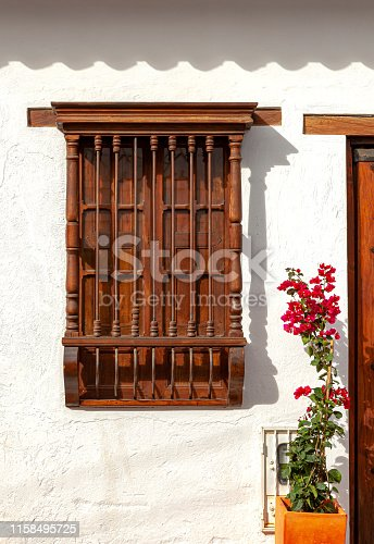 An old Spanish colonial window facing a street, in the 16th century town of Villa de Leyva in Colombia, South America. It is an example of Spanish colonial architecture. Founded in 1572 and located at just over 7000 feet above sea level on the Andes Mountains, Villa de Leyva was declared a National Monument bu the Colombian Government in 1954 to protect its colonial architecture and heritage. It is located in the Department of Boyacá, in Colombia. Photo shot in the morning sunlight; vertical format. No people.