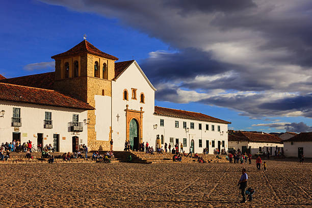 Villa de Leyva, Colombia: The Old Church On The Plaza Mayor Or Main Square In The Historic 16th Century Andean Town At Sunset. Copy Space Villa de Leyva, Colombia - September 13, 2014: The old church on the main plaza or square at sunset time; people visiting the town and local residents are seen on the square just sitting and relaxing, chatting with friends or going about their routine chores. Founded in 1572 and located at just over 7000 feet above sea level on the Andes Mountains, Villa de Leyva was declared a National Monument in 1954 to protect it's colonial architecture and heritage. It is located in the Department of Boyaca, in the South American country of Colombia.  Photo shot in the evening sunlight; horizontal format. Copy space. chandra dhas, stock pictures, royalty-free photos & images