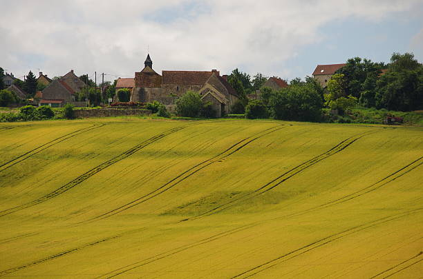 Village and field Montigny-lès-Condé, France - Jul 6, 2012: A typical small quiete french village placed at the top of a hill and a beautiful wheat field on its slope. picardy stock pictures, royalty-free photos & images