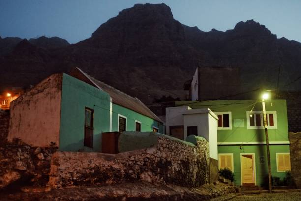 village at night with the ever so typical colorful buildings underneath the towering cliffs stock photo