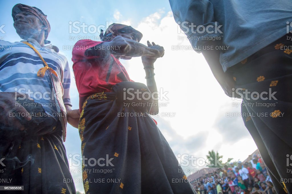 Village Elder Lights a Cigarette at a Traditional Boxing Match stock photo