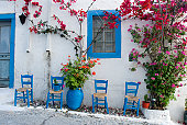 Four blue painted chairs standing in front of a typical white painted Greek village house on the island of Kos with bougainvillea