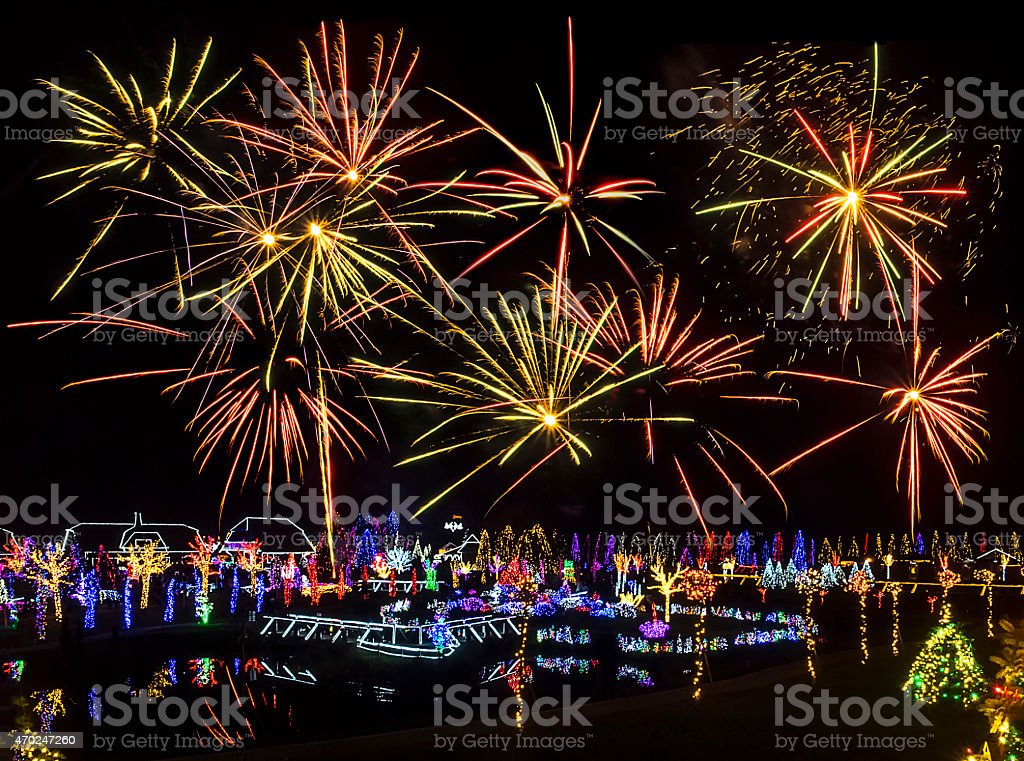 Village illuminated with Christmas lights under fireworks stock photo