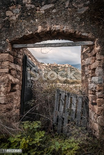 The ancient village of Montemaggiore in the Balagne region of Corsica viewed through the stone entrance of a derelict building