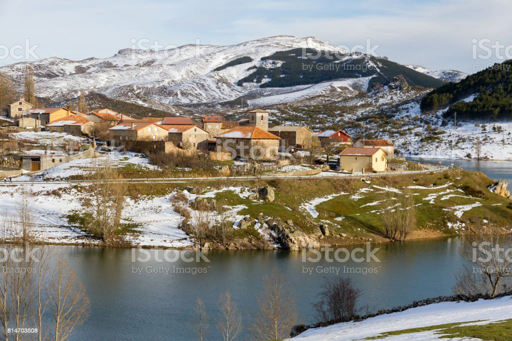 Village of mountain snow on the slope of a reservoir in winter - Pueblo de Montaña Nevado en la ladera de un Embalse en Invierno stock photo