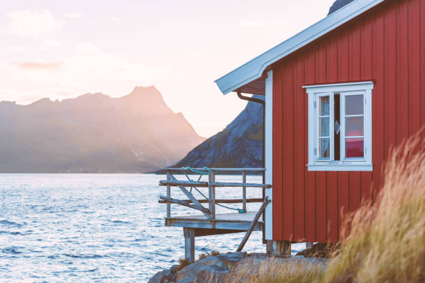 Village of Reine on Lofoten islands in Norway. Traditional red wooden houses and mountains. Sunset sky with clouds. Travel in Scandinavia, Europe. stock photo