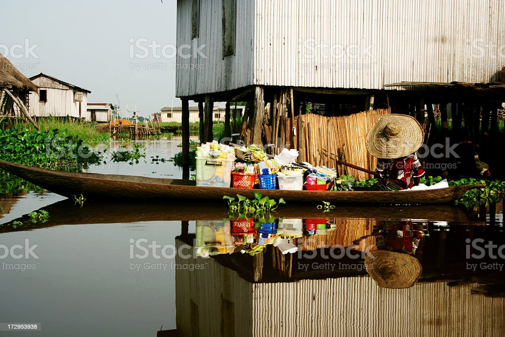 Village on water with a person on a long boat stock photo