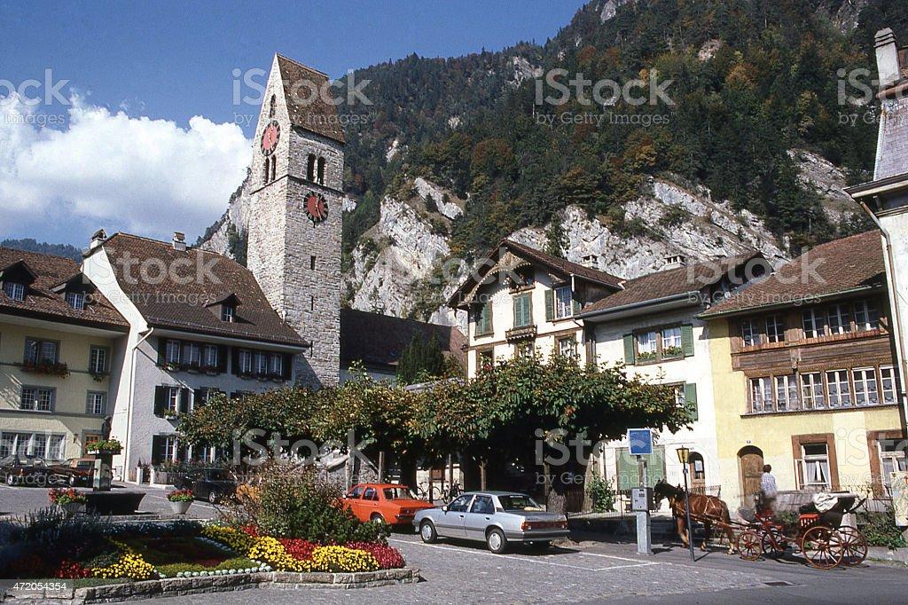Village Plaza clock tower against rocky cliffs Interlaken region Switzerland stock photo