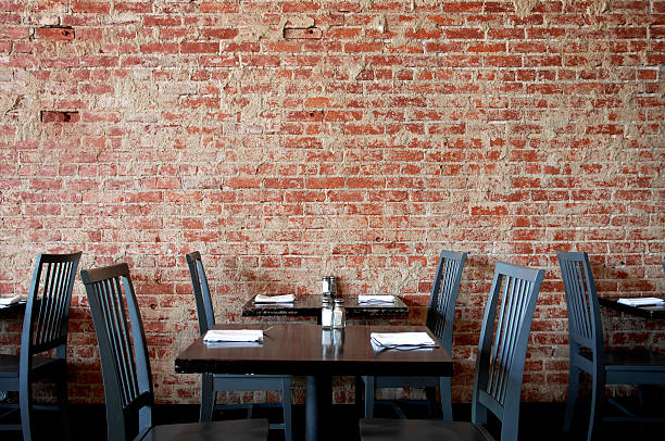 Village Pub Brick Wall with Tables and Chairs stock photo