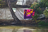 A colourful scene of  clothes drying on a rope tied to a palm tree and a village hut in the back - typical rural life seen while travel through the beautiful backwaters of God's own country, Kerala.