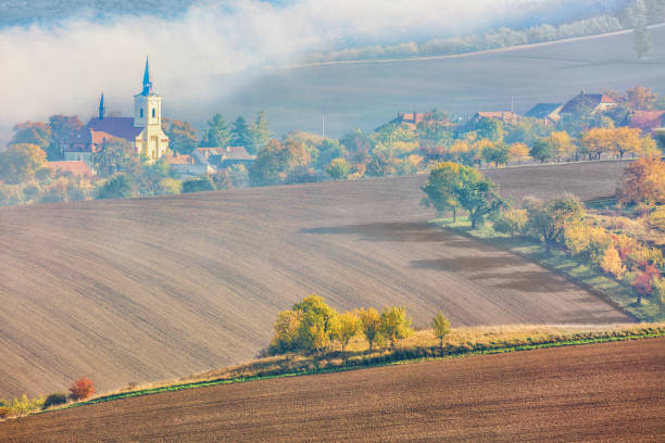 A village with a church in the South Moravian Region. beautiful landscape during sunrise with fog, fields and colorful autumn trees in Czech Republic. A village with a church in the South Moravian Region. beautiful landscape during sunrise with fog, fields and colorful autumn trees in Czech Republic moravia stock pictures, royalty-free photos & images