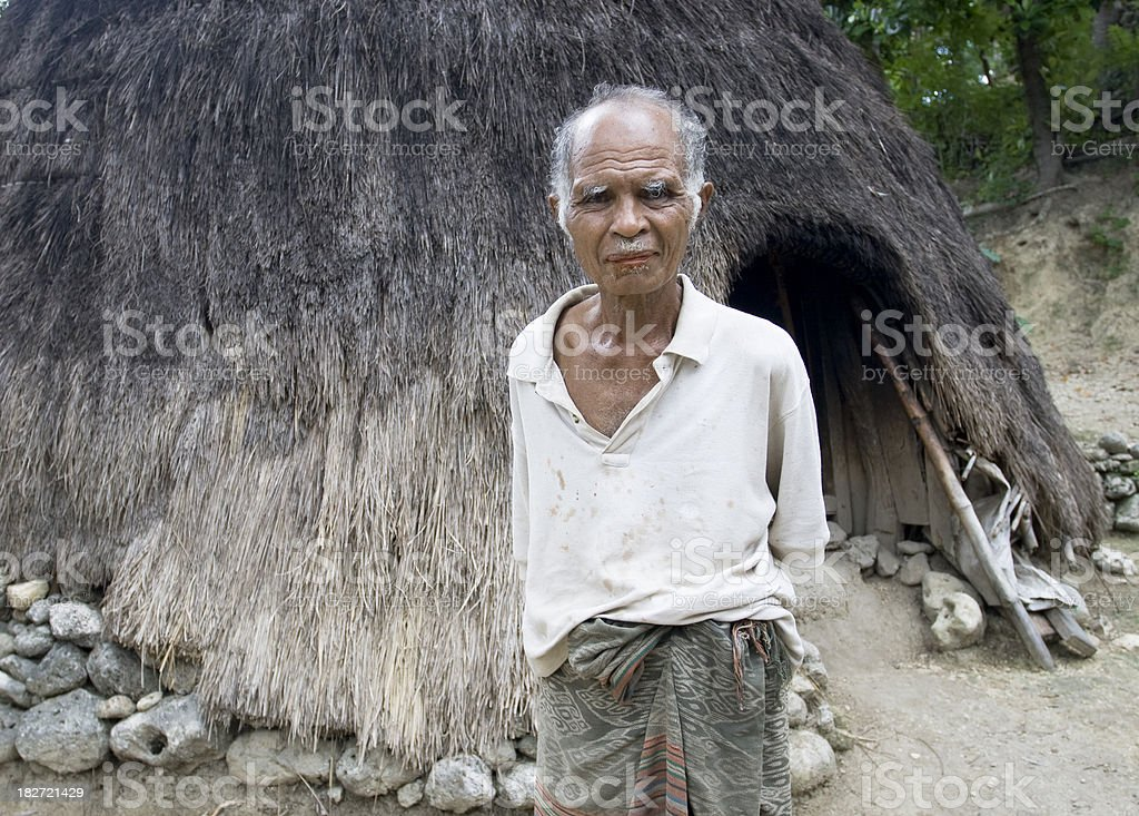 Villager in front of traditional house. stock photo