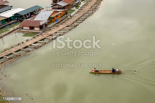 Kanchanaburi, Thailand - Jul 27 2014 : Villager paddle wooden boat in dam,lifestyle tradition culture