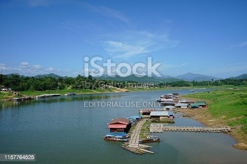 Kanchanaburi, Thailand - June 22 2019 : Wooden house floating on dam in the river with fishing boat at evening