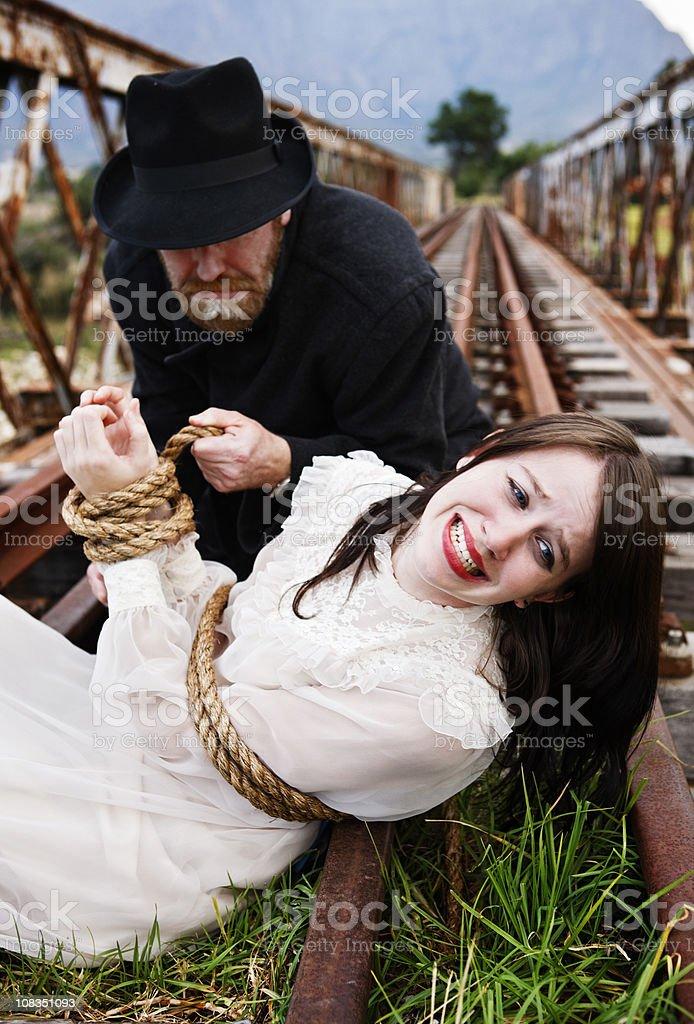Schurke Krawatten Ein verzweifelter maiden von Eisenbahnschienen im viktorianischen melodrama – Foto