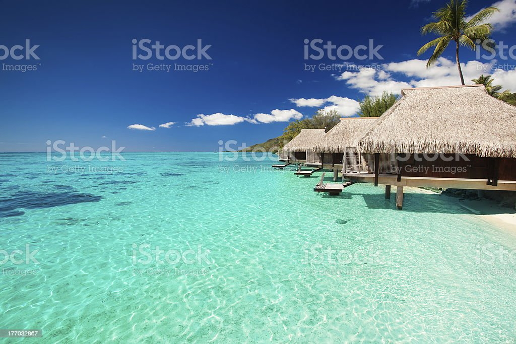 Villas on the tropical beach with steps into water stock photo