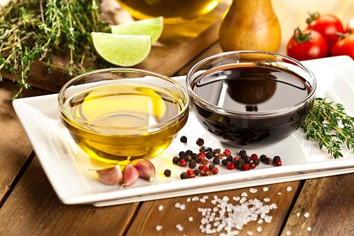 Vinaigrette ingredients on rustic wood table. Olive oil and balsamic vinegar in a bowls, salt, pepper and garlic. DSRL studio photo taken with Canon EOS 5D Mk II and Canon EF 70-200mm f/2.8L IS II USM Telephoto Zoom Lens
