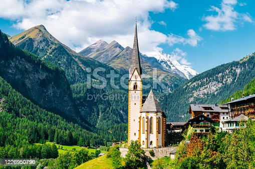 Pfarrkirche - Heiligenblut am Großglockner. Vincent Church, surrounded by Austrian Alps mountains in a sunny day.