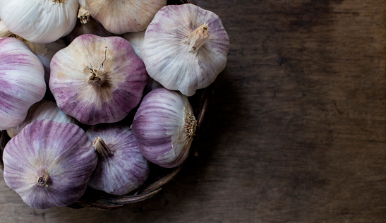 Vine basket full of whole purple Garlic, on top of a wooden background, with copy space