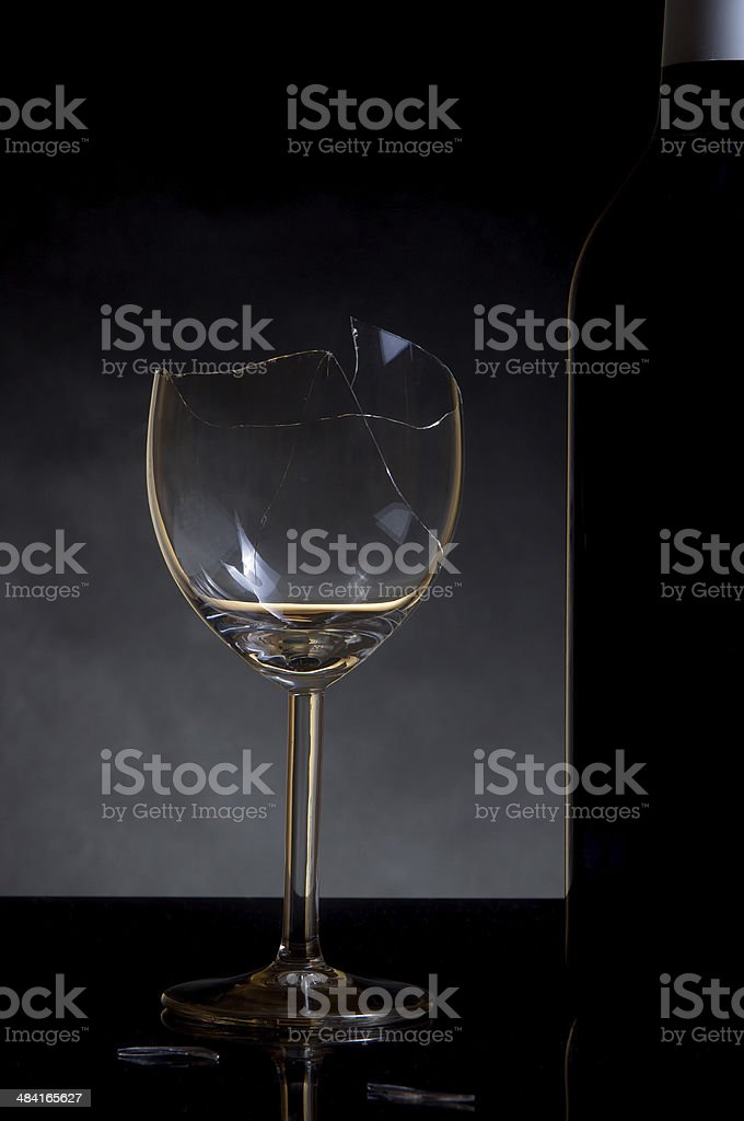 Vine bottle and broken glass on dark background stock photo