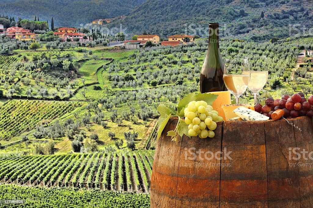 Vine landscape with wine still-life in Chianti, Tuscany, Italy White wine with barrel on vineyard in Chianti, Tuscany, Italy 2015 Stock Photo
