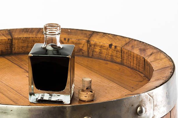 vinegar bottle balsamic vinegar bottle isolated with a barrel balsamic vinegar stock pictures, royalty-free photos & images
