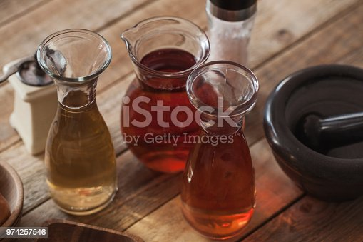 Aromatic vinegar making - vine and apple vinegar with ingredients at wood table
