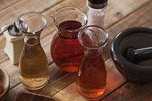 Aromatic vinegar making - vine and apple vinegar with ingredients at wood table