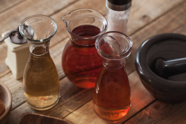 Vinegar in glass at wood table, close-up stock photo