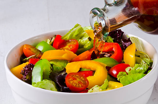 Vinegar pouring into salad bowl stock photo