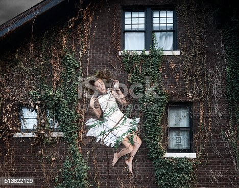 A powerful force has swept a barefoot Caucasian girl wearing a white summer dress up onto the exterior of a brick house and held there by entangling her in vines and branches in this digitally altered image