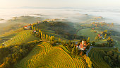Aerial view of scenery with vineyards, trees and houses on hills at sunrise with fog, Jeruzalem, Slovenske Gorice, Prlekija, Styria, Slovenia