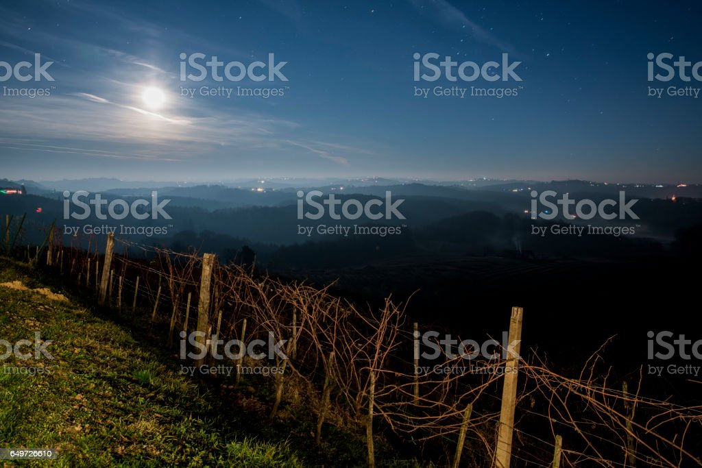 Vineyards on silhouette hills against sky stock photo
