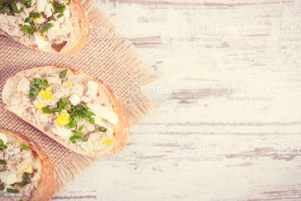 Vintag photo, Baguette with mackerel or tuna fish paste, copy space for text on rustic plank stock photo