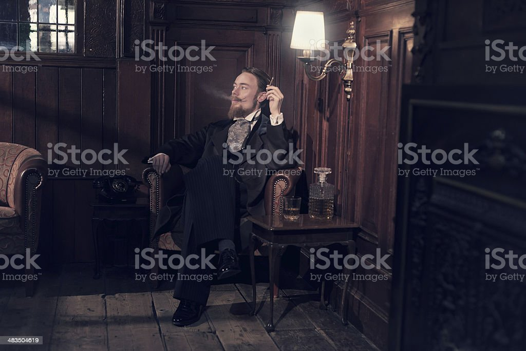 Vintage 1900 fashion man with beard. Sitting in old room. stock photo