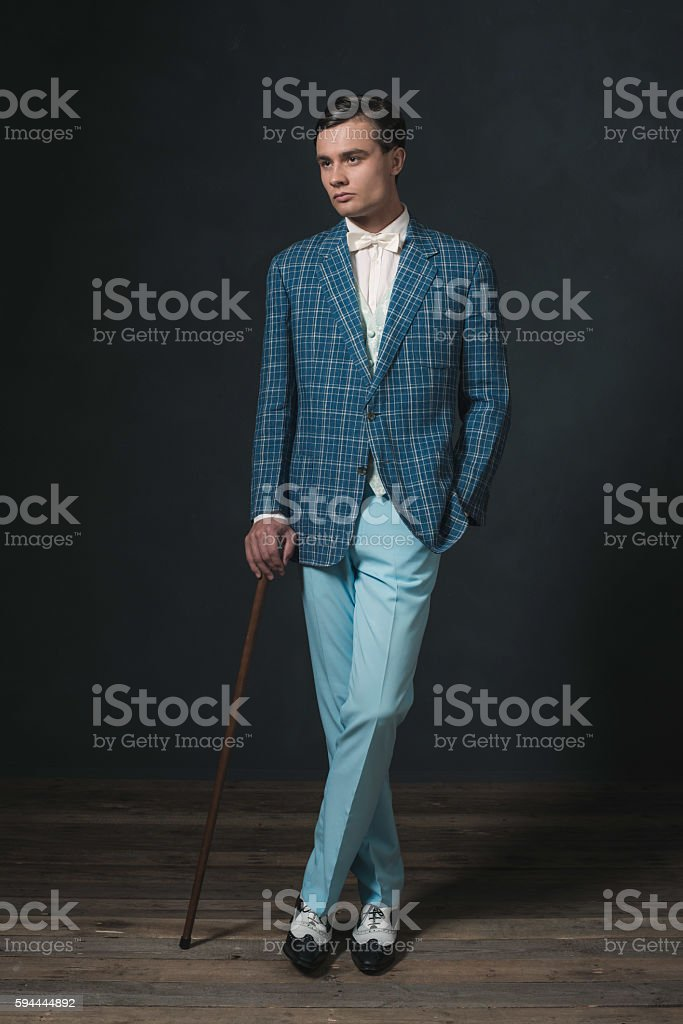Vintage 1920s well dressed young man standing with cane. stock photo