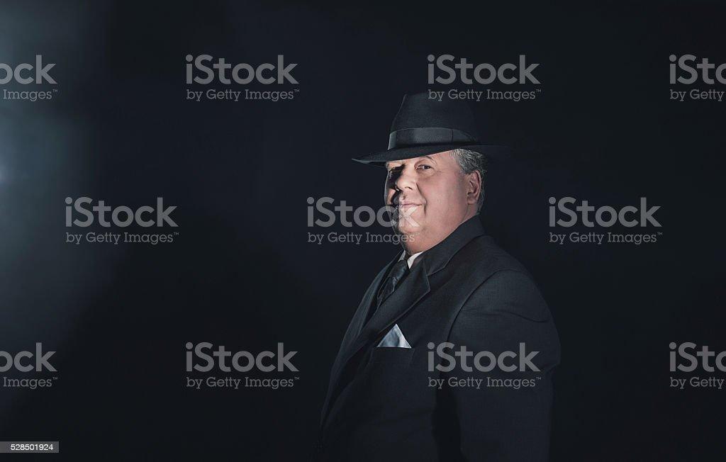 Vintage 1930s gangster wearing hat. Classic studio portrait. stock photo