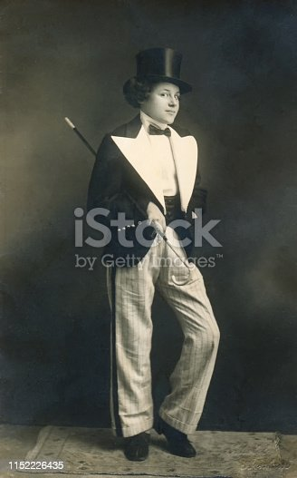 Vintage 1930s portrait of a young girl with curly hair and black top hat, holding a baton and wearing a classic black and white tap dance outfit.