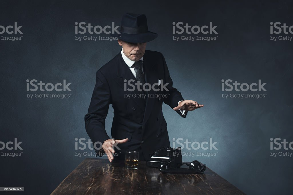 Vintage 1940 businessman grabbing whiskey after calling. stock photo