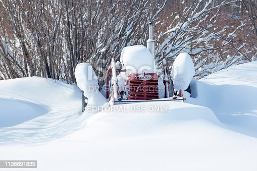 Erskine, USA - March 10, 2019: A vintage 1940 Farmall H tractor with  a loader and bucket is covered and surrounded with fresh snow after a Minnesota blizzard.