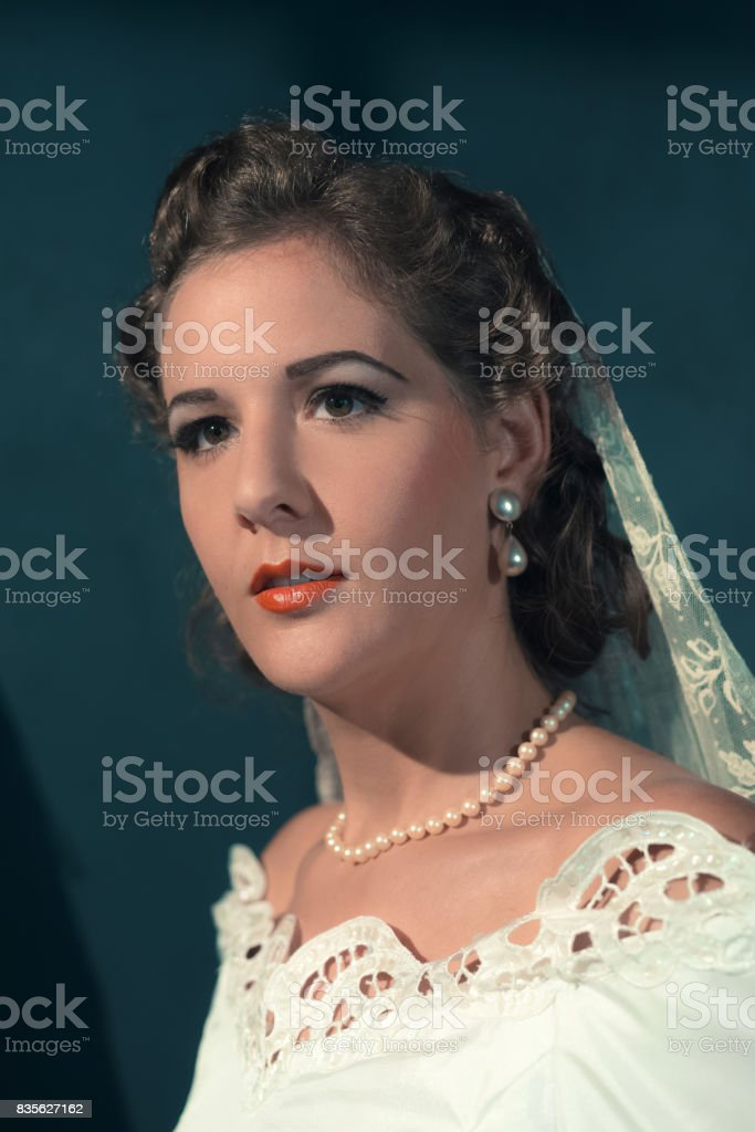 Vintage 1940s bride in white dress and pearl necklace. Studio head shot. stock photo