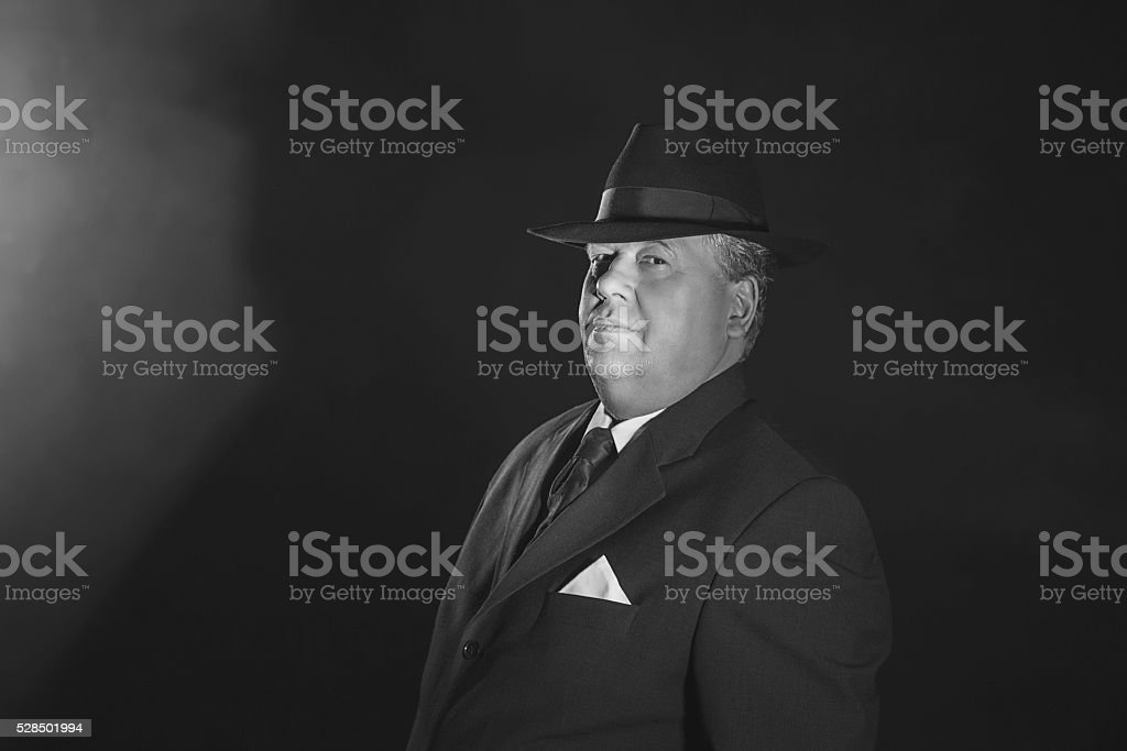 Vintage 1940s gangster wearing hat. Classic black and white portrait. stock photo