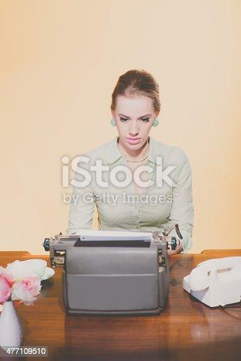 istock Vintage 1950 blonde secretary woman sitting behind desk working 477109510
