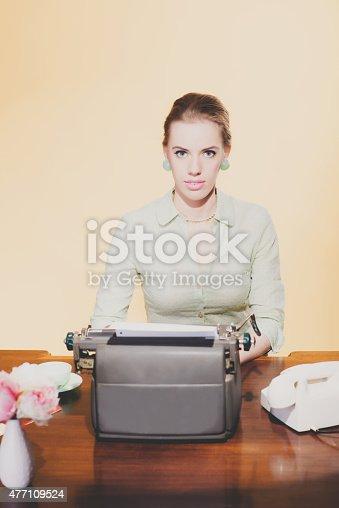 istock Vintage 1950 blonde secretary woman sitting behind desk working 477109524