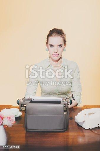 istock Vintage 1950 blonde secretary woman sitting behind desk working 477109544