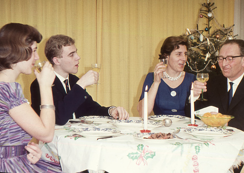 Vintage 1950´s image: family enjoying the Christmas holidays with a dinner.