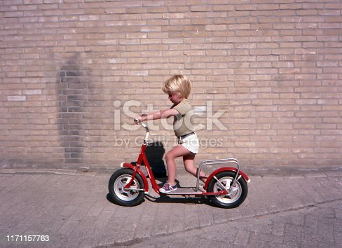 Vintage 1970s image of a young boy with blond hair on a red retro kick scooter shot against a brick wall.
